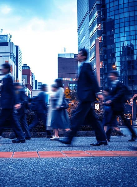 People in motion blur walking down the road of a city
