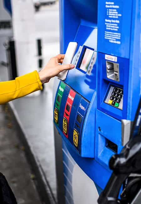 A woman pays for her gas wirelessly using her phone.