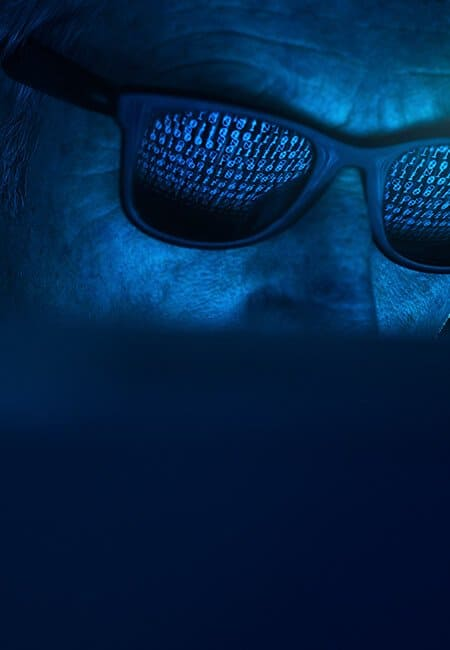 A close up shot of a man's face with sunglasses on. He is in a dark room and the computer screen is reflected in his sunglasses showing lines of binary code.