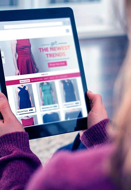 A woman browses a shopping website on her tablet.