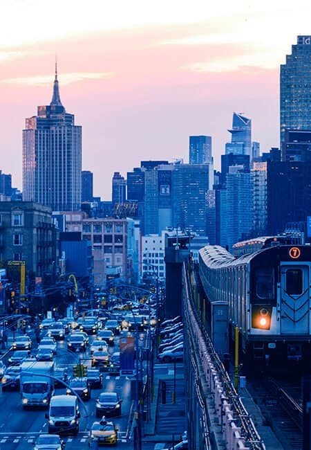 City scape at sunset from the train tracks with train coming and traffic below