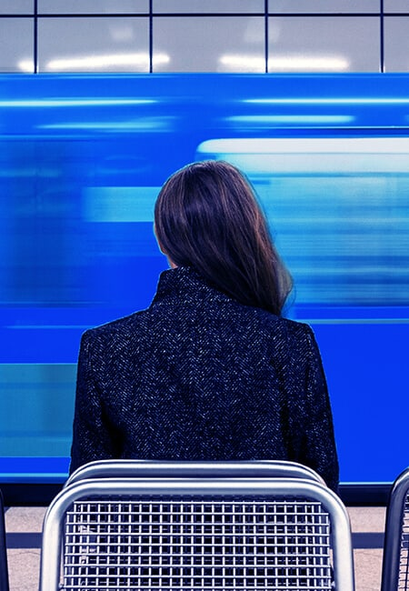 A woman sits in a train station, there is a blue train speeding past in a blur of motion.